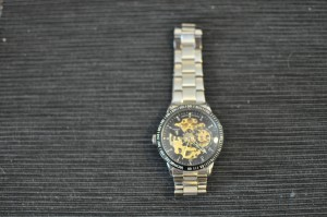 Metallikello, musta kellopiha, josta näkee näppärästi koneistoon. Kuriositeettikello.